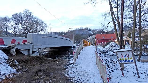 NOVÝ MOST VYROSTL na silnici č. 1973 v Tasnovicích. Měl být hotový v prosinci 2015, ale termín bylo nutné prodloužit. Rychlost je zde omezena na 30 km/h a chodci řeku zdolávají po provizorní lávce.