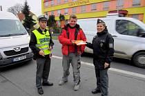Tisková mluvčí policistů Domažlicka Dagmar Brožová předává jednomu z řidičů reflexní vestu.