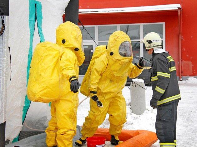 Hasiči v protichemických oblecích se dekontaminují před domažlickým zimním stadionem.