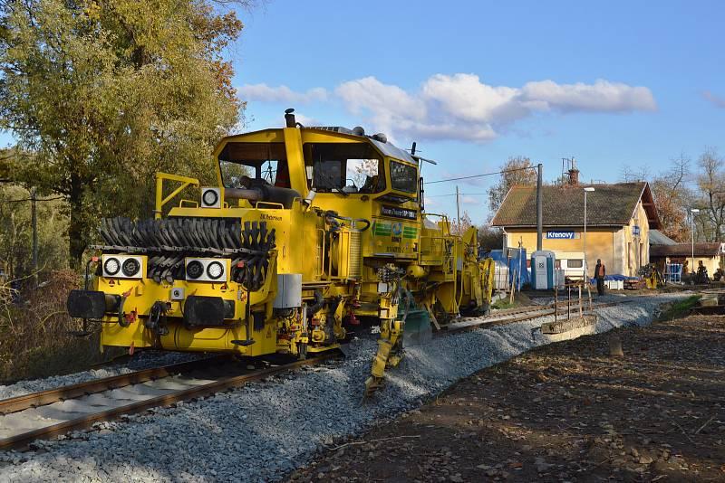 Pracovní stroj pluhem upracuje štěrkové lože poblíž železniční stanice Křenovy.