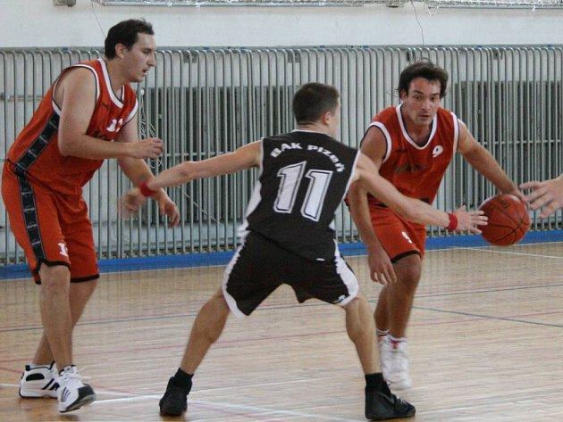 KUDY S MÍČEM DO KOŠE. Holýšovský rozehrávač Petr Přikryl (vpravo) se snažím prosadit přes svého obránce Jana Svíčku (uprostřed).