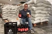 Sládek David Bierhanzl. V jedné ruce drží pivo načepované na degustaci z tanku a ve druhé už stočené do lahve.