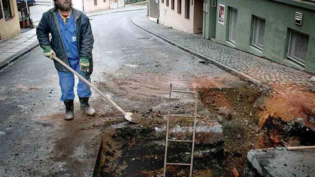 Pracovník Chodských vodáren a kanalizací pracuje na znovunapojení okapové roury a výměně potrubí, které prasklo na rohu ulic Npor. O. Bartoška a Msgre B. Staška