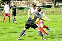 Tomáš Tlustý v dresu Holýšova se snaží probít ke střele přes hráče soupeře.