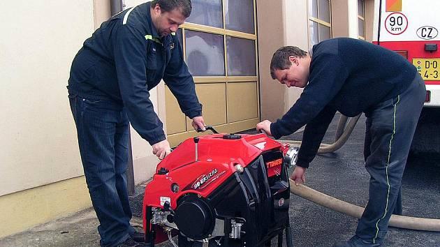 NOVÝ POMOCNÍK. Domažličtí dobrovolní hasiči Petr Svoboda a Tomáš Böhm při záběhu nové stříkačky Tohatsu.