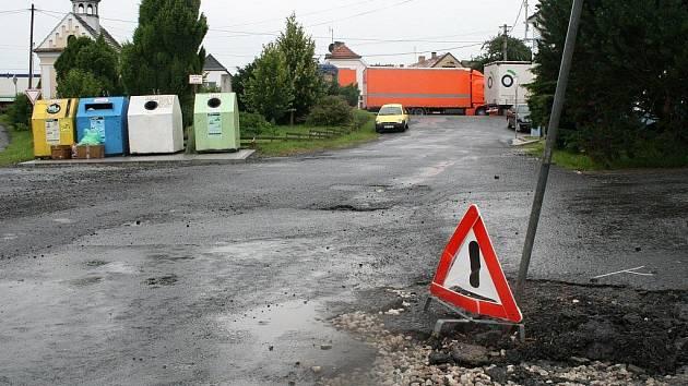 Výstražný červený trojúhelník označuje výmol na silnici v Křenovech. Jde o jeden z mnoha, které v obci vytvořila květnová povodeň.