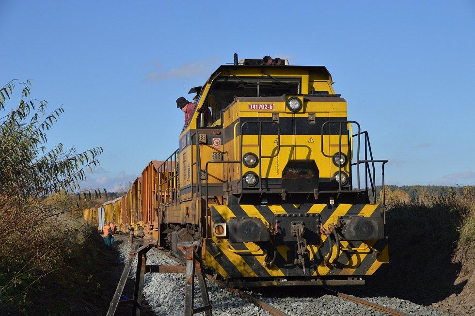 Lokomotiva posunuje s naloženými vozy štěrku.
