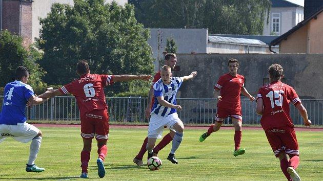 Domažlický Daniel Černý (v modrobílém) právě střílí jediný gól svého týmu do sítě Tachova.