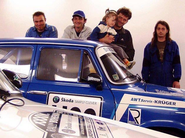 ást týmu v jedné z garáží (zleva): Jan Plas, Roman Svoboda, Bohumír Svoboda ml. s dcerou Terezkou a Jiří Schneider. Vpředu bílé závodní  ´erko´ a modrá tisícovka.
