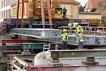 Největší kolový jeřáb v zemi v usadil na opravené pilíře deset betonových nosníků, z nichž se skládá nový most. Ten bude mít širší vozovku i vyšší nosnost. Řidiči se po něm projedou až příští rok.