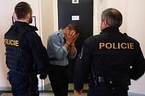 Policisté přivádějí cizince obviněného ze spáchání vraždy ve stadiu pokusu do soudní síně.
