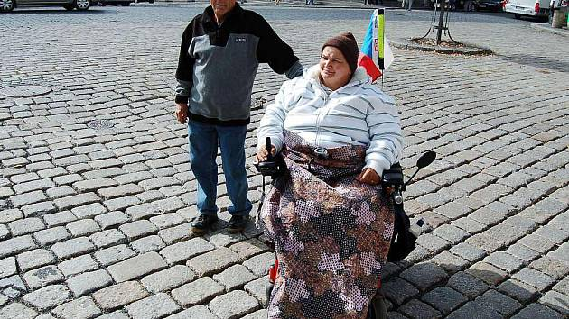 Magda Němcová ze Stráže by bez manžela zůstala doma. Hrůzu jí nahánějí velké spáry mezi kostkami, kam zapadnou kolečka vozíku.