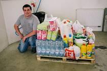 U palety s věcmi, kterými lidé přispěli v sobotu v podvečer, pózuje domažlický hasič Luboš Mleziva.