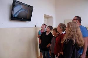 Žáci Masarykovy základní školy se zájmen sledují prostřednictvím kamery, o se děje v poštolčím hnízdě.