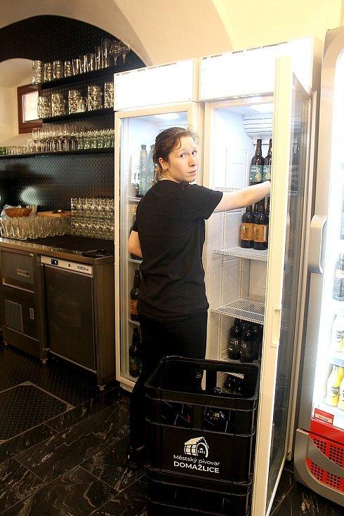 Zaměstnankyně Městského pivovaru Domažlice doplňuje pivo do lednice.