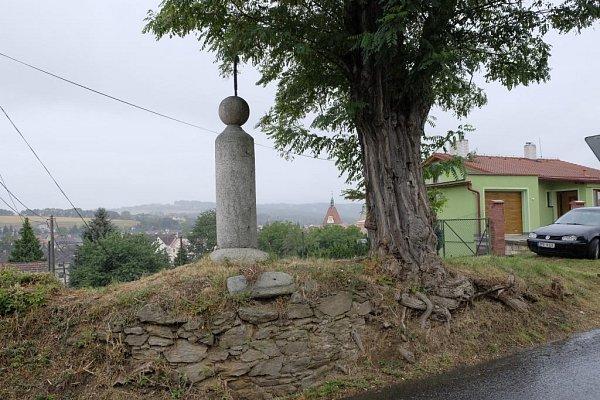 Záběr pochází zkřižovatky ulic Jindřichova a Šumavská. Louka zmizela, nahradilo ji sídliště. Křížek a jeden ze dvou stromů dosud stojí, výhledu překáží dům.