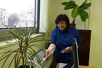 Z VYDÁVÁNÍ PRŮKAZŮ POSTIŽENÝM. Referentka ÚP Domažlice Jana Jarábková laminuje jednomu z příchozích nový průkaz.