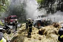 Hasiči likvidují požár sena na valníku.