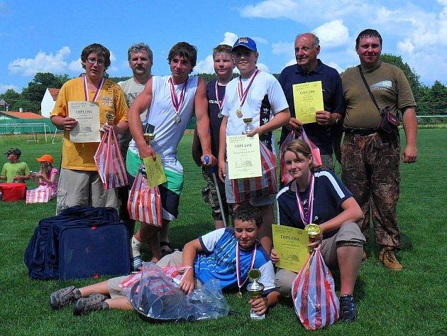 VÍTĚZNÉ DRUŽSTVO z domažlického okresu se svými trenéry a vedoucími pózuje se získanými poháry a diplomy.