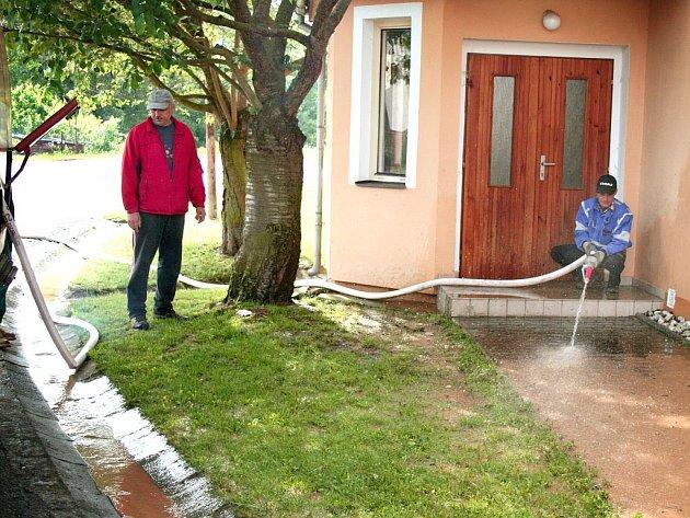 František Volkmann (vlevo) ze Sboru dobrovolných hasičů Křenovy dohlíží na čištění chodníků. Následky rozmarů úterního počasí jsou vytopené sklepy i byty, poškozené silnice i chodníky.