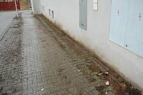 Znečištěný chodník před bytovým domem v Petrovické ulici v Domažlicích.