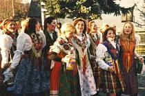 Cestou na Kytičkovou zábavu si mládež v průvodu zpívá a nese s sebou něco na zahřátí.