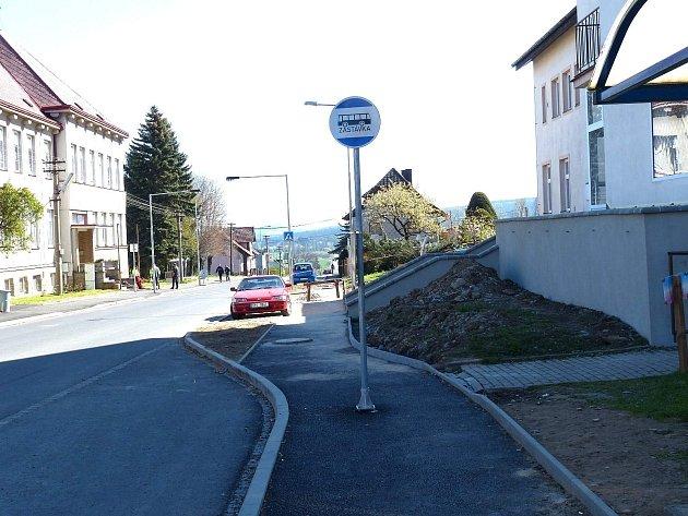 V chodníku je osazen 75 cm od levého obrubníku (měřeno k jeho středu), doprava je průchod o šíři 109 cm.