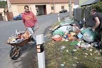 NA NÁVSI VE STRÝČKOVICÍCH pomáhají lidé před domem Marcely Kuchárikové odklízet téměř veškeré vybavení domu, které v noci ze soboty na neděli zničila povodeň.