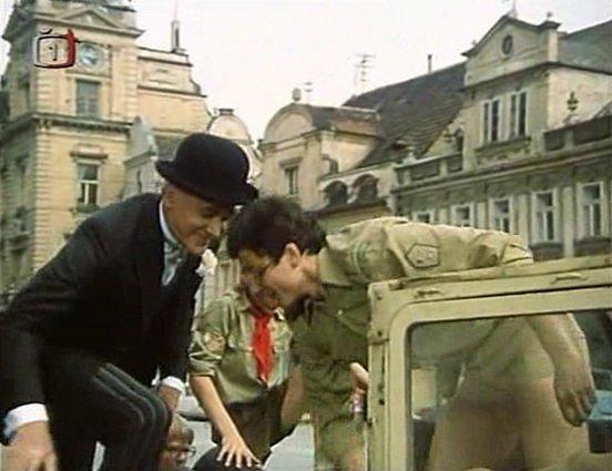 Táborový vedoucí vyzvedává v6. minutě filmu chlapce, které poslal do města pro kuchaře. Tím se stane Pan Tau. Vpozadí domažlická radnice.