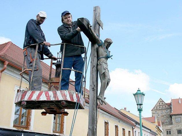 Miroslav Zvonař s kolegou sundavají sochu Krista z dřevěného kříže na mostě v Horšovském Týně.