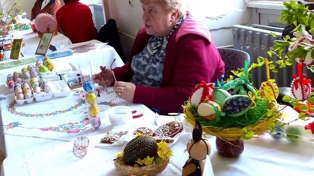 Anežka Červenková oplétá vajíčka drátem a zdobí je korálky. Za košíčkem s kuřátkem je opletené  pštrosí vejce.
