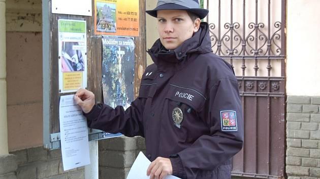 Policistka Dagmar Brožová vyvěšuje letáčky na domažlickém hřbitově.