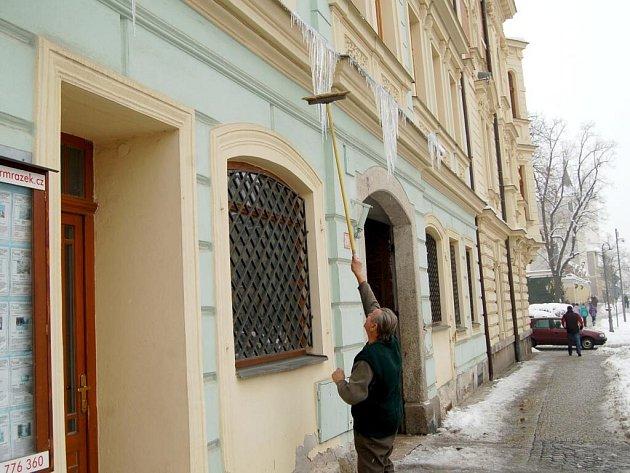 S koštětem v ruce odstraňuje Josef Mathauser v ulici Msgre B. Staška v Domažlicích rampouchy. Jeden z nich mu poranil ruku.