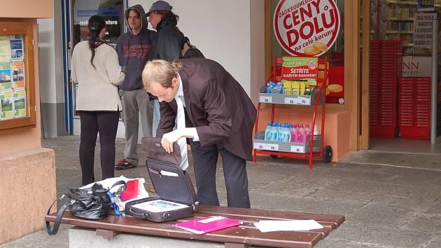 POČKAT, JEN SI JEŠTĚ NĚCO VYNDÁM. Skupina dealerů si odchytla kolemjdoucí a nabízí jim výhodný tarif od společnosti O2. Zatímco dealer hledá ještě nějaké podklady, jeho kolegyně zdrží odchycené a začne jim vše vysvětlovat.