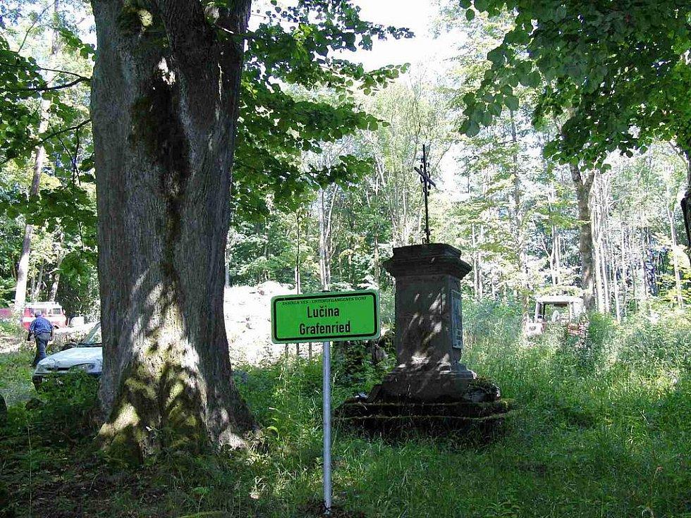 V místě zaniklé obce Lučina. Před započetím současných prací obec připomínala tato tabulka a podstavec opatřený křížem.