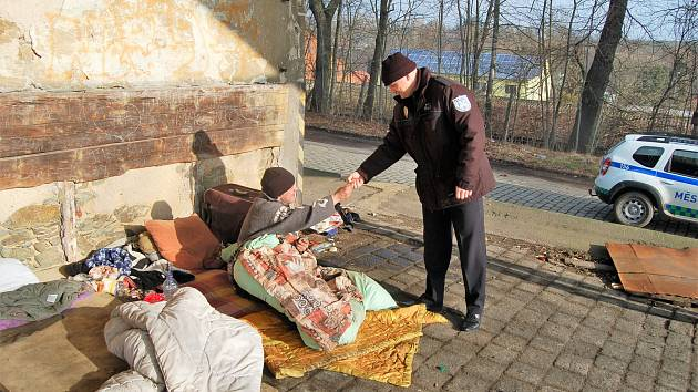 MĚSTSKÁ POLICIE pravidelně kontroluje bezdomovce v Domažlicích. Na snímku velitel městské policie Petr Kubal legitimuje muže přespávajícího u domažlického nádraží.