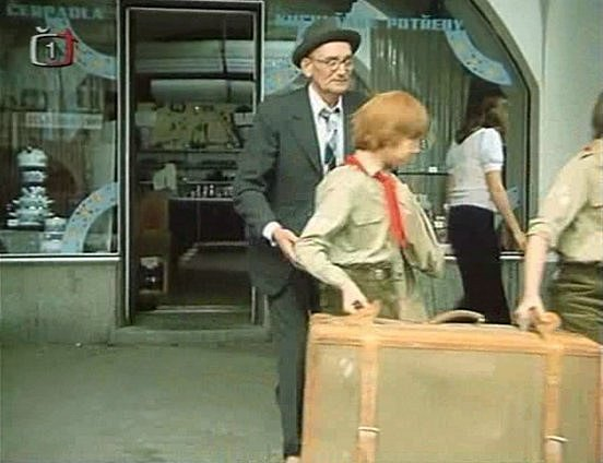 V5. minutě kuchař (Václav Lohniský) naléhá na pionýry, aby ho dovedli do tábora. Stojí před železářstvím, které nahradilo kuchyňské studio Gorenje.