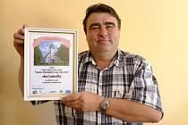 Starosta Luženiček František Kopecký drží čestný diplom, který jeho obec získala.