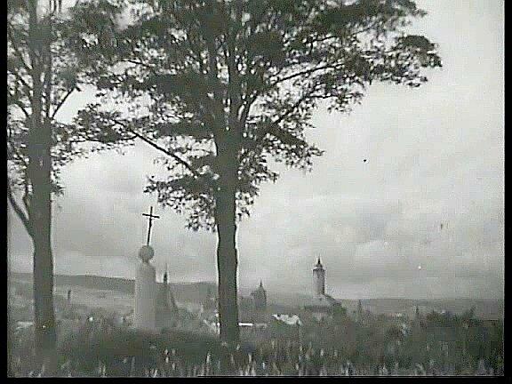 Záběr z5. minuty filmu poprvé představuje město Domažlice pohledem přes křížek, dva stromy a louku. Záběr podkresluje píseň Žádnyj neví co sou Domažlice.