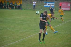 Útočník Tlumačova Martin Wolf (ve žlutém dresu) bojuje ve výskoku o míč s obráncem Rapidu Plzeň.