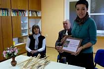 """Z PŘEDÁNÍ CERTIFIKÁTU V DPS HOLÝŠOV. Hana Valachovičová (stojící) ocenila dvojí verzi certifikátu: """"Zanedlouho si tam mohou dát ten vánoční."""" Uprostřed starosta Antonín Pazour, vlevo pak inspektorka distribuce Domažlického deníku Milada Mlezivová."""