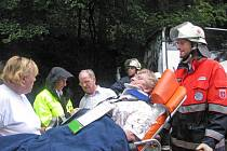 Německý záchranář nakládá zraněnou ženu do sanitky.