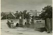 Historička Kristýna Pinkrová připravuje publikaci o historii Bělé nad Radbuzou a okolí. Na snímku je kamenný most přes Radbuzu, v pozadí obecná škola.
