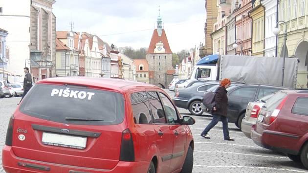 KUDY TUDY CESTIČKA? Chodci se při přecházení domažlického náměstí proplétají mezi vycouvávajícími i projíždějícími vozy.