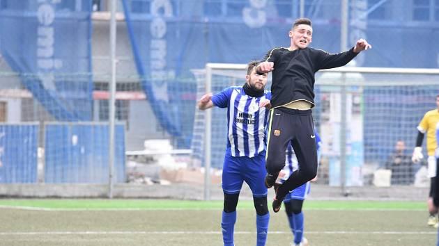 Záložník Domažlic Pavel Javorský (na snímku v modrobílém dresu vzadu) ve výskoku s hostujícím hráčem Vasilem Zajcevem (v černém dresu).
