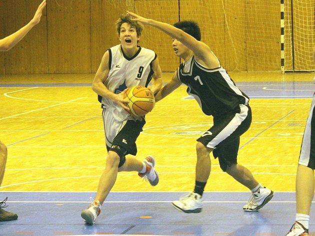 Domažlický basketbalista Jan Kozina při průniku obranou Brandýsa.