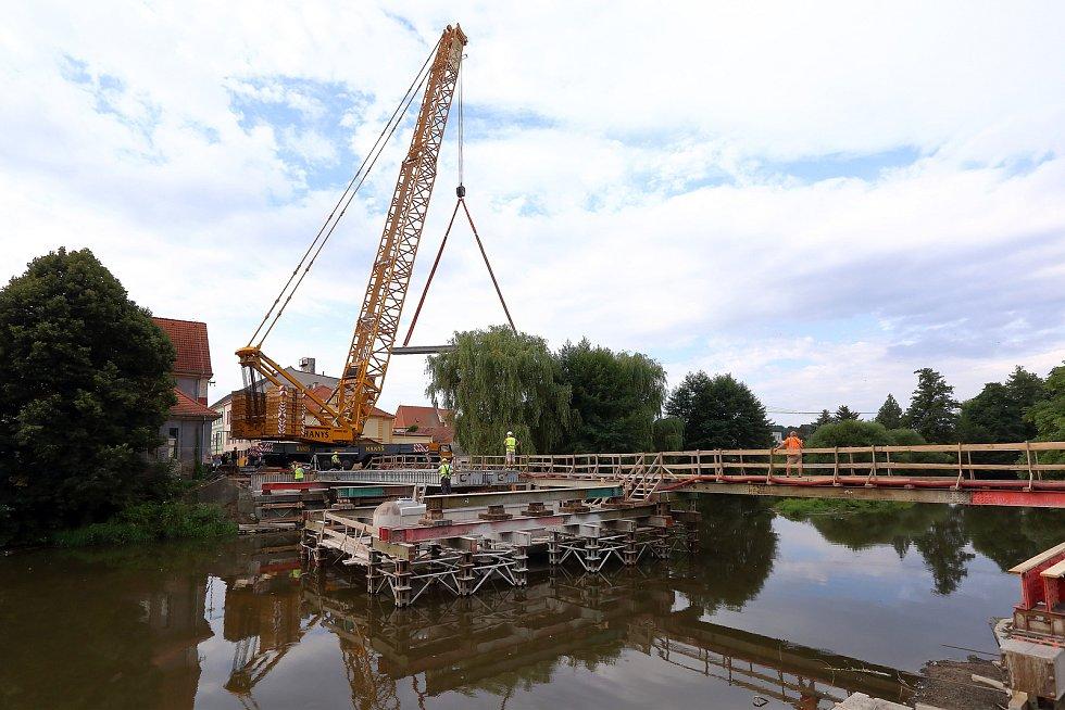 Největší kolový jeřáb v zemi v pondělí usadil na opravené pilíře deset betonových nosníků, z nichž se skládá nový most. Ten bude mít širší vozovku i vyšší nosnost. Řidiči se po něm projedou až příští rok.