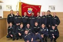 Členové jednotky Sboru dobrovolných hasičů Holýšov pózují u prapor sboru.