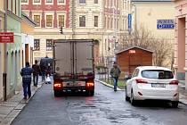 ÚZKÁ KOSTELNÍ ULICE V DOMAŽLICÍCH. Proplétají se v ní chodci i automobily.