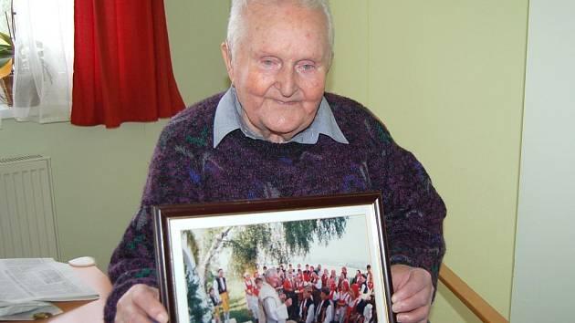 MONS. VLADISLAV SYSEL ukazuje fotografii z natáčení filmu v Postřekově, kterého se také zúčastnil.